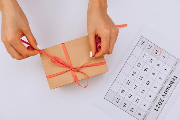 Des mains féminines ouvrent un cadeau sur fond blanc à côté d'un calendrier festif avec une marque du 14 février. la saint-valentin
