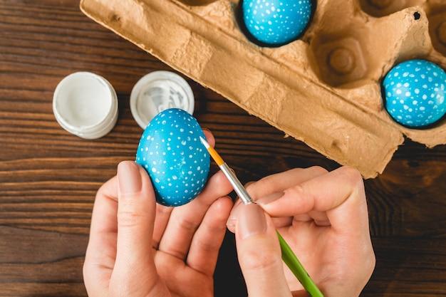 Mains féminines peint des oeufs de pâques bleus avec un pinceau, vue de dessus