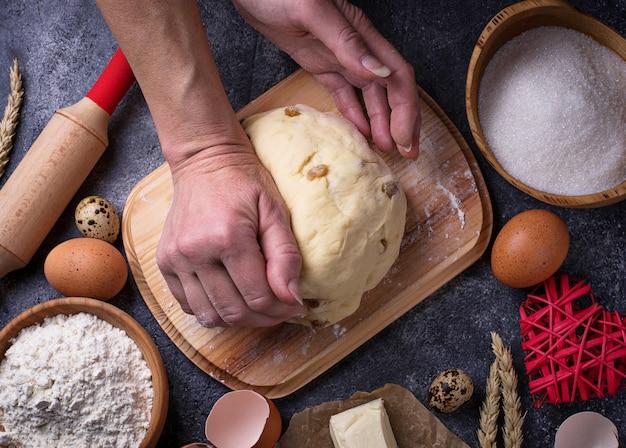 Des mains féminines pétrissent la pâte. concept d'accompagnement. vue de dessus