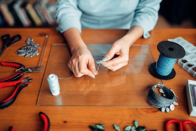 Mains féminines avec des pinces, vue de dessus, travaux d'aiguille
