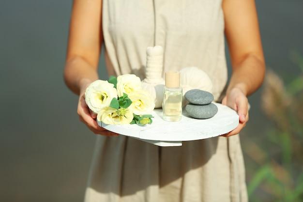 Mains féminines avec plateau de produits de spa, à l'extérieur