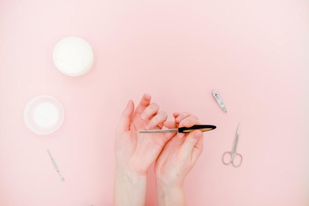Mains féminines avec un pot de crème blanche et un kit de manucure, des ciseaux, un polisseur. concept de soins de la peau.