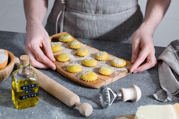 Mains féminines, processus de préparation des pâtes italiennes faites maison, ravioli - cuisine italienne