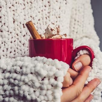 Mains féminines, pull blanc et tasse rouge
