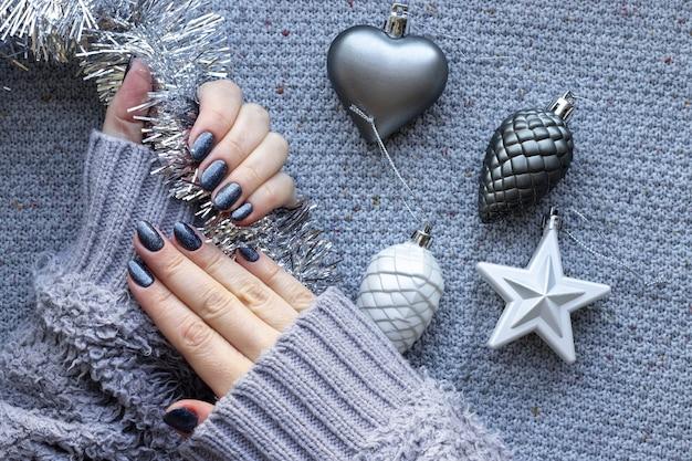 Mains féminines en pull avec des ongles scintillants bleus