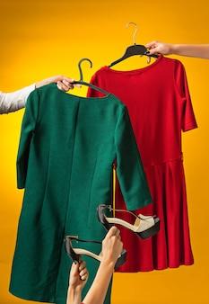 Les mains féminines avec des robes en mains sur jaune. le concept d'achat et de vente