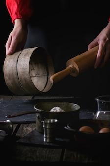 Mains féminines avec rouleau à pâtisserie et tamis en bois