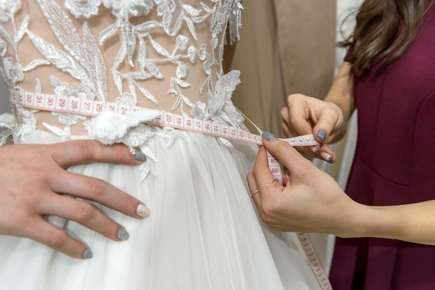 Mains féminines avec ruban à mesurer sur la taille de la robe de mariée