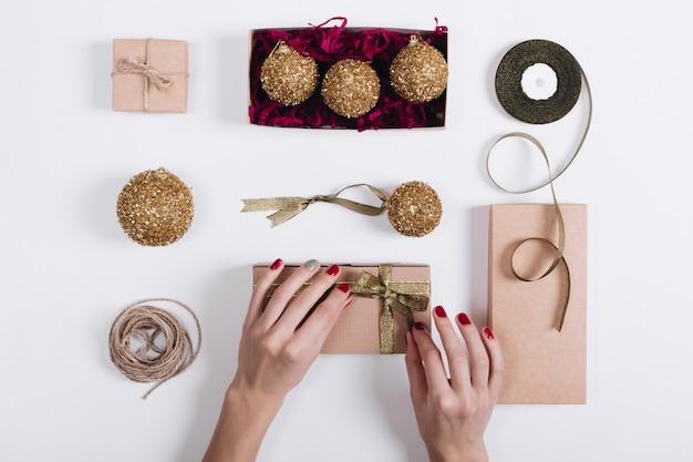 Mains féminines avec un ruban rouge manucure attaché sur la boîte avec un cadeau