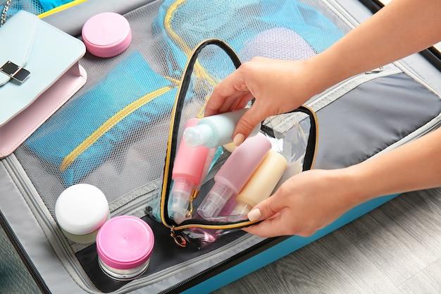 Mains féminines, sac avec kit de cosmétiques de voyage et valise sur le sol