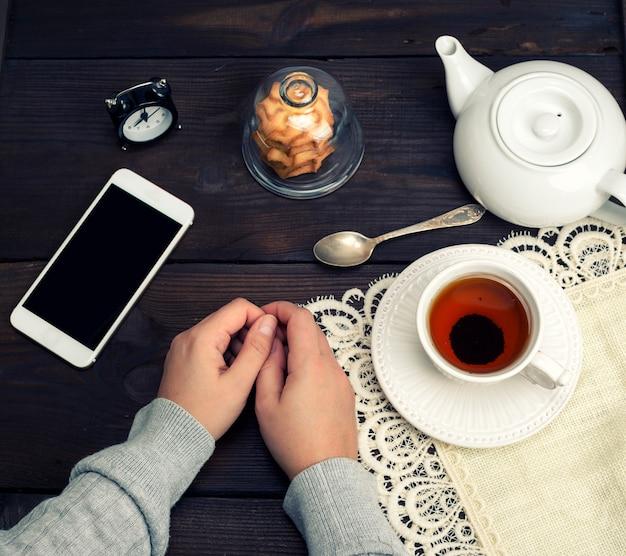 Des mains féminines se trouvent sur une table en bois, à côté d'une tasse de thé et d'un smartphone