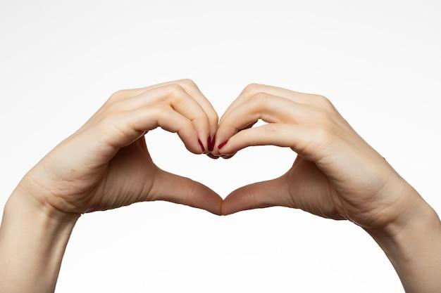 Mains féminines avec un signe en forme de coeur