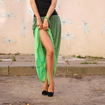 Mains féminines soulevant jupe longue