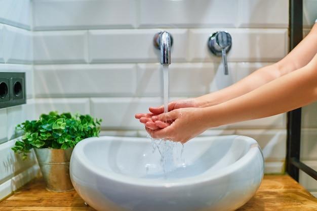 Mains féminines sous l'eau du robinet dans la salle de bain à la maison. prévention et protection contre les infections, les bactéries, les germes et les virus