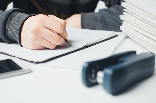 Mains féminines avec un stylo écrivant sur un ordinateur portable
