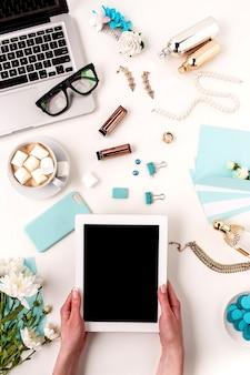 Les mains féminines et la tablette contre les objets de femme de mode bleu sur blanc. concept de maquette féminine