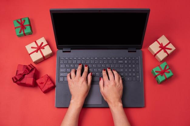 Mains féminines tapant sur un ordinateur portable avec des cadeaux sur fond rouge, travaillant pendant les vacances, concept de noël.