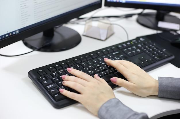 Mains féminines tapant sur ordinateur