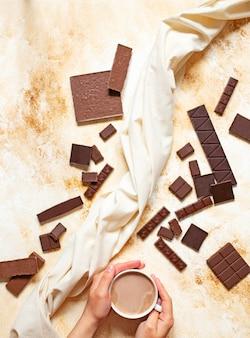 Mains féminines avec une tasse de cacao sur un fond de marbre clair. assortiment de différents types de chocolat. vue de dessus, pose à plat. espace pour le texte. verticale.