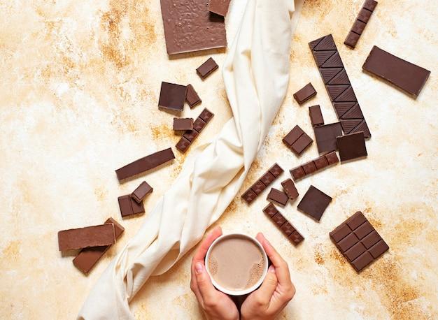 Mains féminines avec une tasse de cacao sur un fond de marbre clair. assortiment de différents types de chocolat. vue de dessus, pose à plat. espace pour le texte.
