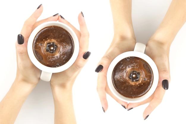 Mains féminines avec une tasse de thé blanc vue de dessus main féminine avec une tasse de café noir sur le dessus de table blanc
