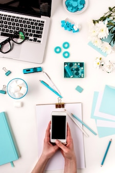 Les mains féminines et le téléphone intelligent contre les objets de femme de mode bleu sur blanc. concept de maquette féminine