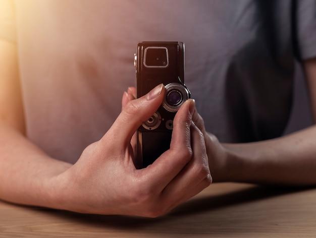 Mains féminines tenant l'ancien appareil photo argentique vintage rétro objectif photo