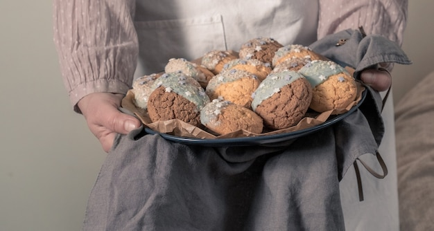 Mains féminines tenant une assiette avec des biscuits pour baby shower party