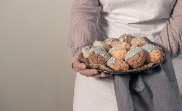 Mains féminines tenant une assiette avec des biscuits
