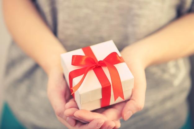 Mains féminines tenant beau petit cadeau enveloppé de ruban de satin.