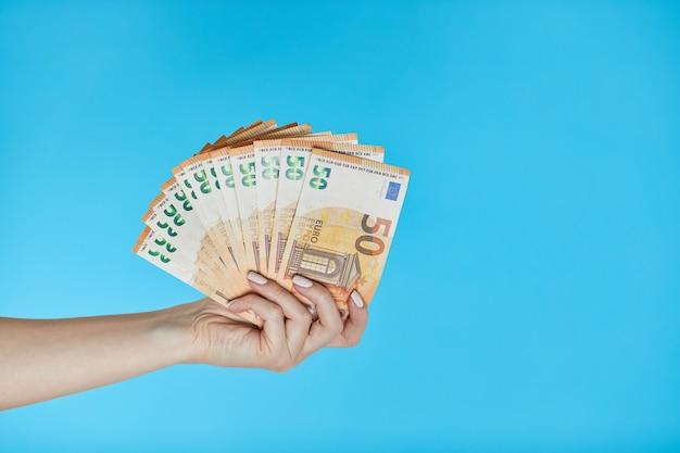 Mains féminines tenant des billets en euros sur bleu.
