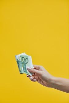 Mains féminines tenant des billets en euros