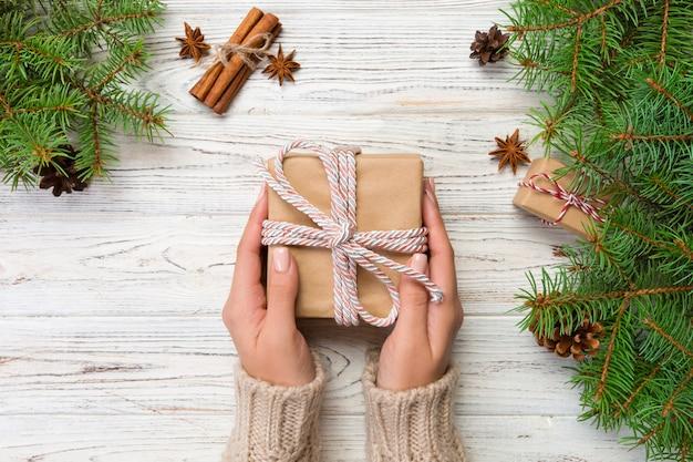 Mains féminines tenant la boîte actuelle à la main en papier recyclé sur une table en bois blanche. concept de préparation de noël, emballage cadeau