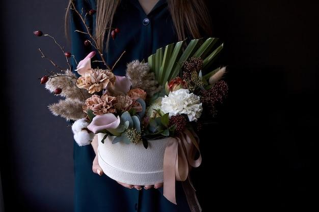Mains féminines tenant une boîte avec un bouquet vintage sur un fond sombre
