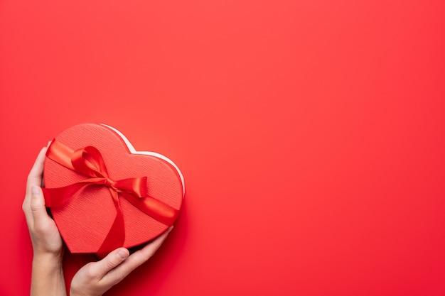 Mains féminines tenant boîte cadeau coeur rouge sur fond rouge. composition de la saint-valentin