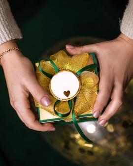 Mains féminines tenant une boîte cadeau enveloppée dans du papier vert avec un arc en or.