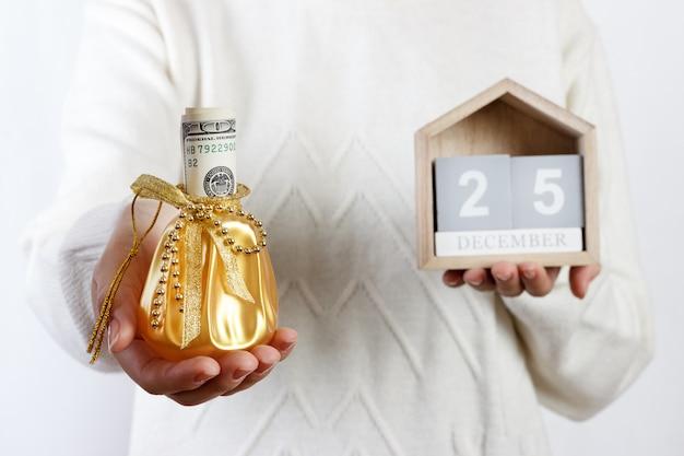 Mains féminines tenant une boîte de cadeau de noël avec dollar et calendrier, noël, 25 décembre, cadeau de vacances et décoration