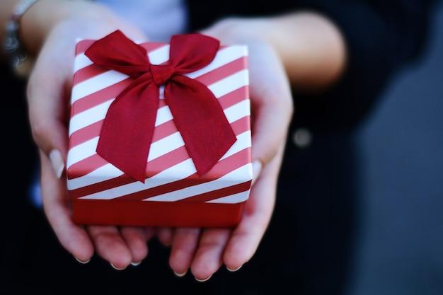 Mains féminines tenant une boîte-cadeau, présente.