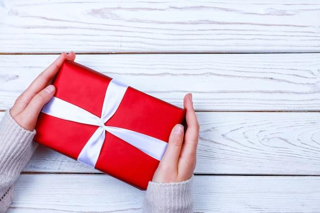 Mains féminines tenant une boîte cadeau rouge avec ruban sur fond de bois