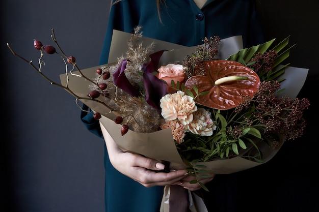 Mains féminines tenant un bouquet décoré dans un style vintage sur un fond sombre