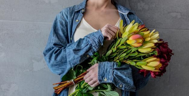Mains féminines tenant un bouquet de pivoines et de leucadendron