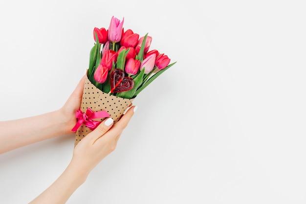 Mains féminines tenant un bouquet de tulipes, enveloppées dans du papier et décorées de ruban