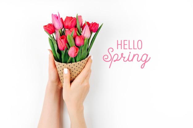 Mains féminines tenant un bouquet de tulipes enveloppées dans du papier