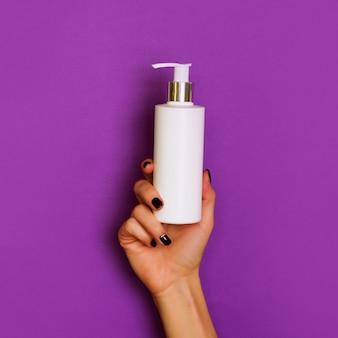 Mains féminines tenant une bouteille cosmétique blanche sur fond violet