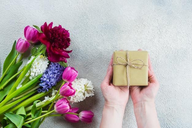 Mains féminines tenant un cadeau ou une boîte cadeau, fleurs tulipes, pivoine, jacinthe sur une table en bois