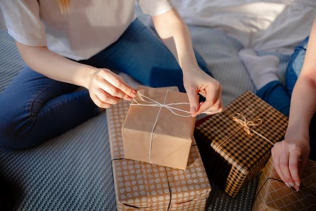 Mains féminines tenant cadeau. présent enveloppé de papier kraft. concept de vacances vue horizontale supérieure.