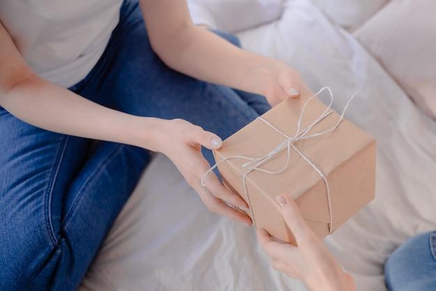 Mains féminines tenant cadeau. présent enveloppé de papier kraft.