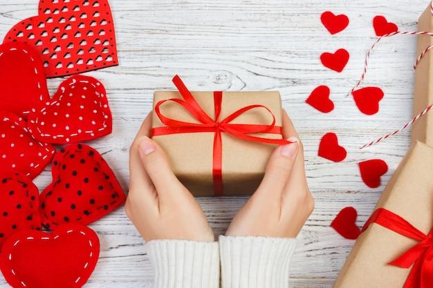 Mains féminines tenant un cadeau de saint valentin