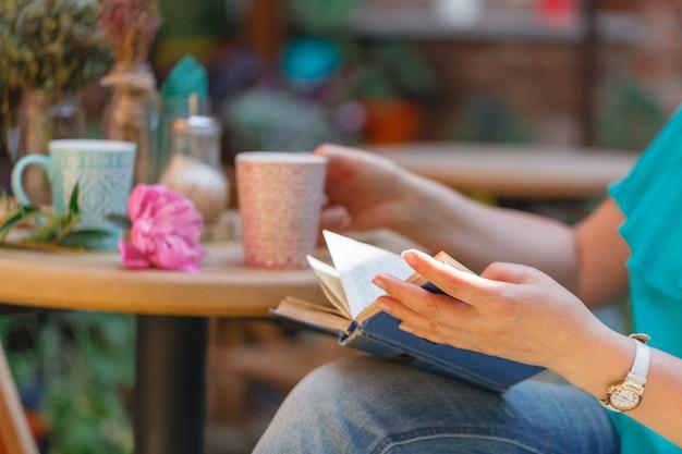 Mains féminines tenant le café du matin et livre à table de café