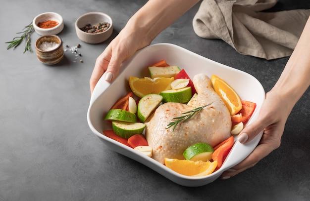 Mains féminines tenant une casserole en céramique avec de la viande de poulet crue et des légumes dîner festif